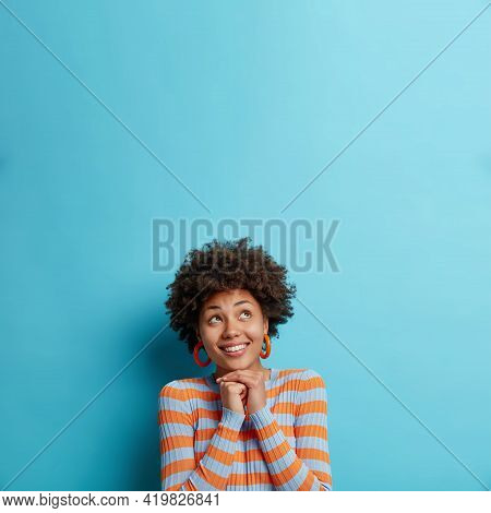 Vertical Shot Of Pleased Young Afro American Woman Keeps Hands Under Chin Focused Upwards Happily Dr