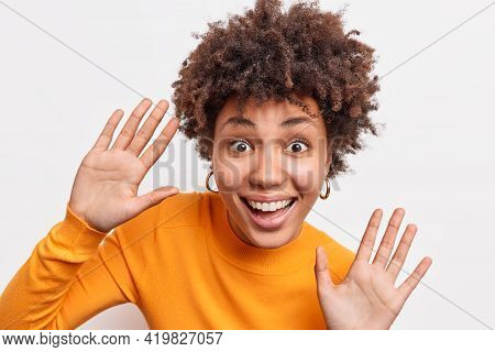 Expressive Playful Curly African American Woman Smiles Broadly Raises Palms High Foolishes Around Ha