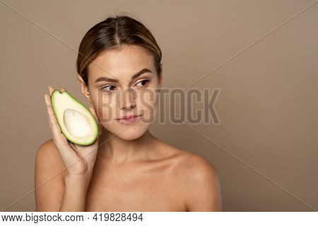 A Beautiful Woman Holds Half An Avocado In Front Of Her Face. Photo Of An Attractive Woman With Perf