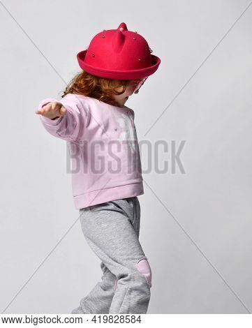 Cute Little Smiling Shy Preschool Girl Wearing Red Hat, Sporty Pink Gray Unicorn Print Clothes Takin