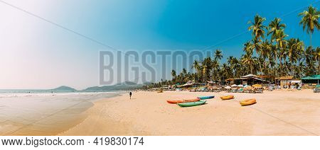 Canacona, Goa, India. Canoe Kayak For Rent Parked On Famous Palolem Beach On Background Tall Palm Tr