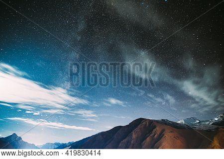 Stepantsminda, Georgia. Natural Real Night Starry Sky With Milky Way Galaxy Glowing Stars Over Peak