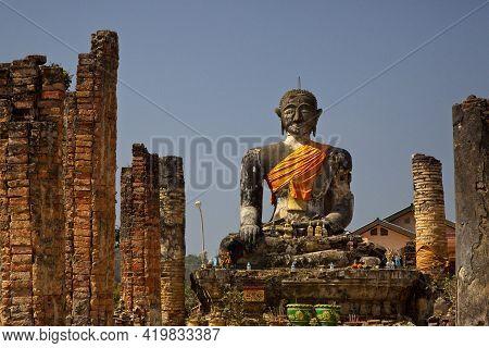 Huge Stone Statute Of Buddha Looking Forward Wrapped In Orange Clock Monastry Phonsavan, Laos.