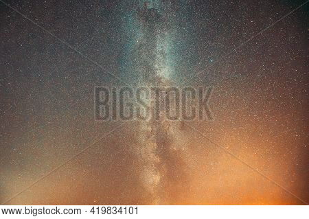 Milky Way Galaxy In Night Starry Sky With Glowing Stars. Bright Glow Of Sky In Lights Of Sunset Dawn