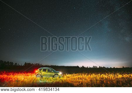 Milky Way Galaxy In Night Starry Sky With Glowing Stars Above Green Car Suv In Countryside Landscape