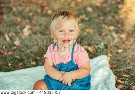 Smiling Caucasian Happy Baby Girl Sitting On Blanket On Ground Outdoors In Autumn Fall Park. Funny C