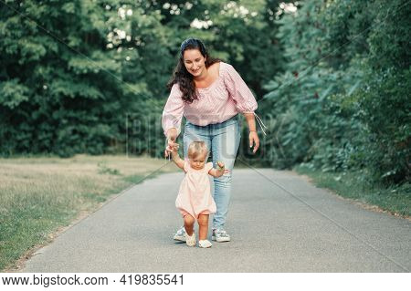 First Steps Of Baby. Cute Baby Girl Learning To Walk And Holding Her Mother Hand. Mom Helping Toddle