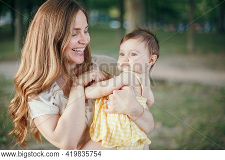 Mothers Day. Middle Age Smiling Caucasian Mother And Girl Toddler Daughter Playing In Park. Mom Embr