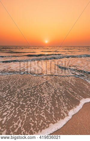 Sunset Sun Above Sea. Natural Sunrise Sky Warm Colors Over Ripple Sea. Ocean Water Foam Washing Sand