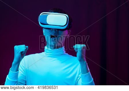Excited Asian Young Man Wearing Vr Headset In Neon Light, Future Technology Concept.