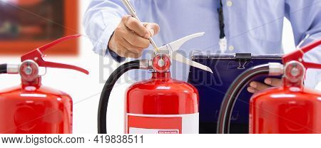 Fire Extinguisher, Firefighter Checking Pressure Gauge Level Of Fire Extinguisher Tank In The Buildi