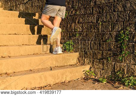Cropped View Of Fitness Runner Woman Training Herself By Running Up Steps On Staircase In Urban Stre