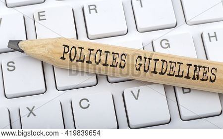 Text Policies Guidelines On Wooden Pencil On White Keyboard. Business