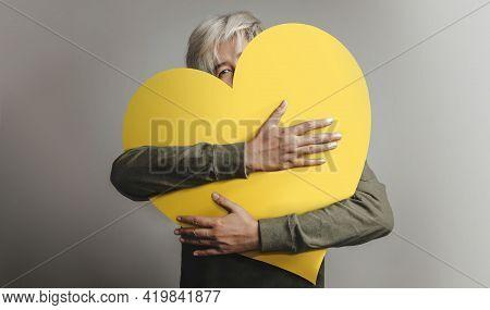 Love Yourself Concept. Happy Person Embracing Self, Hugging A Big Heart. Looking Into Camera. Positi