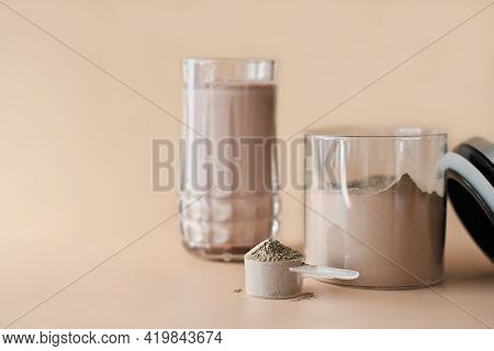 Scoop Of Collagen Peptides Powder With Chocolate Flavor In A Jar And Protein Shake In A Glass. Suppl