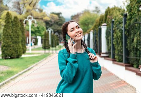 Portrait Of A Pretty Smiling Woman With Pigtails Talking On The Phone. In The Background There Is An