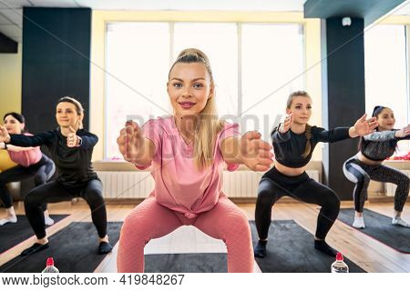 Young Woman Doing Squat Exercise At Group Fitness Training With Other People Girls Standing In Row W