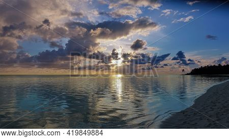 Maldives Sunset. In The Evening Sky, There Are Picturesque Cumulus Clouds, Orange And Pink Illuminat