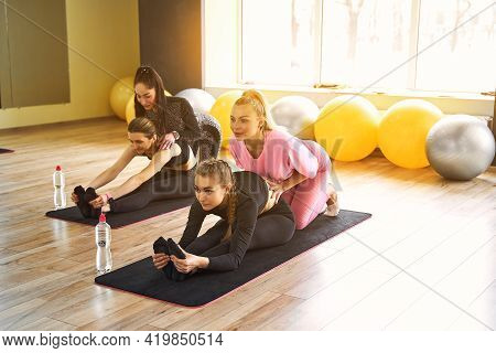 Young Active Women With Slim Body Doing Stretching Exercise To Keep Fit, Body Flexibility On Yoga Ma