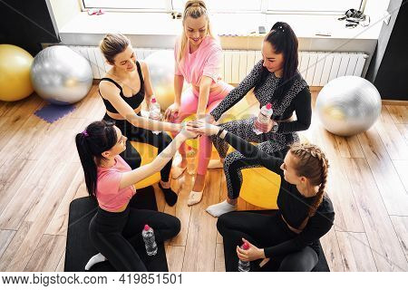 Group Of Fit Happy People Giving High Five In Fitness Studio Room, Talking In A Circle After Seminar