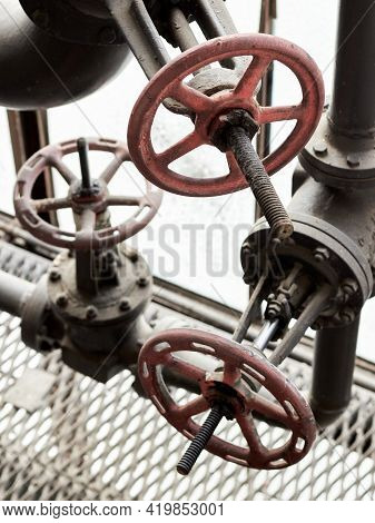 Three Metal Red Industrial Valves With Flywheel On Chemical Pipe With Oil Seals Bolts And Nuts Close