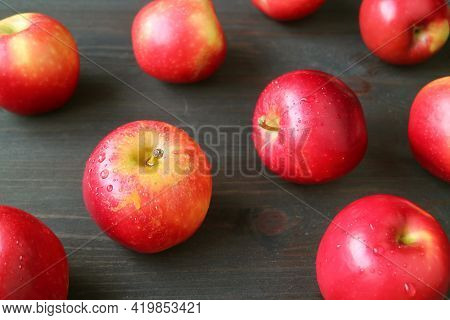 Closeup Red Fresh Ripe Apples With Water Droplets Scattered On Dark Brown Wooden Table