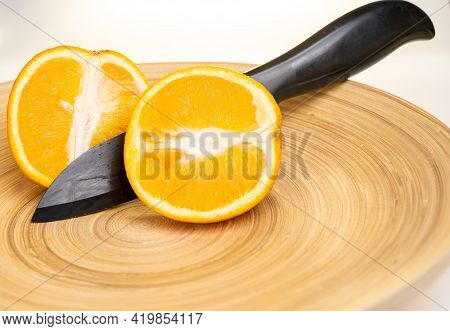 Two Halves Of One Sliced Yellow Juicy Orange And A Black Knife With Which The Orange Is Cut Lie In A