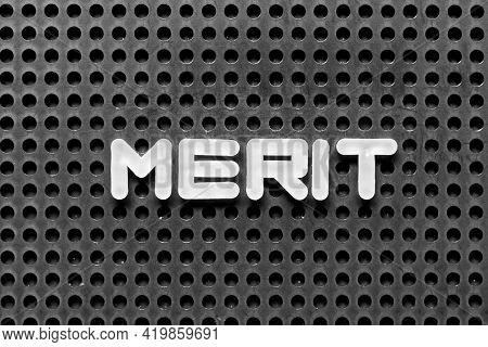 White Alphabet Letter In Word Merit On Black Pegboard Background