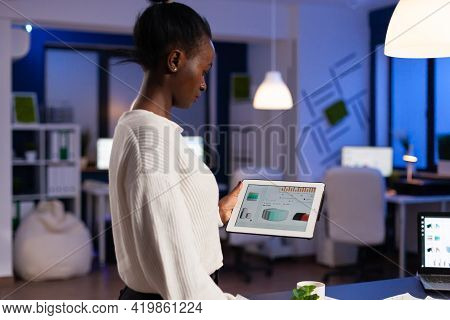 Black Woman Working On Deadline Analysing Charts On Tablet Pc