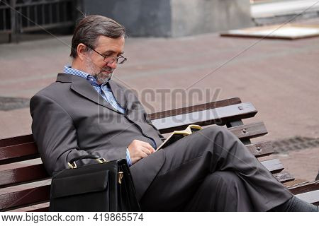 Moscow, Russia - May 2021: Man In Eyeglasses And Business Suit Sitting With A Leather Briefcase On A