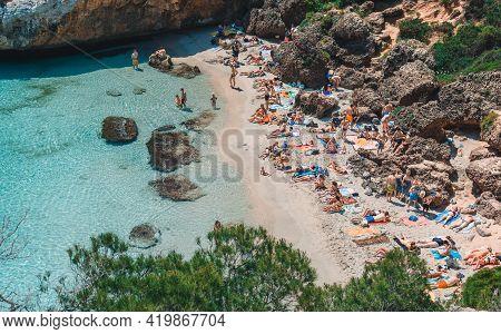 Mallorca, Spain: May 22, 2018: Calo Del Moro Beach, Santanyi. Crowded Mediterranean Beach, Clear Tur
