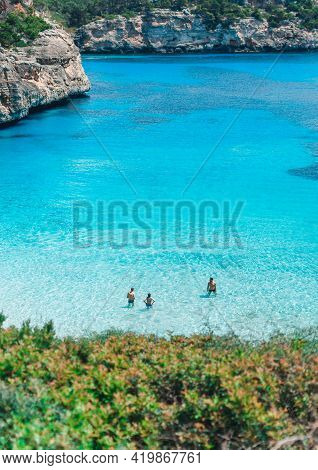 Mallorca, Spain: May 22, 2018: Calo Del Moro Beach, Santanyi.three Persons Standing In Clear Turquoi