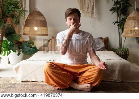 Caucasian Mature Man Practicing Yoga Sitting, Making Alternate Nostril Breathing