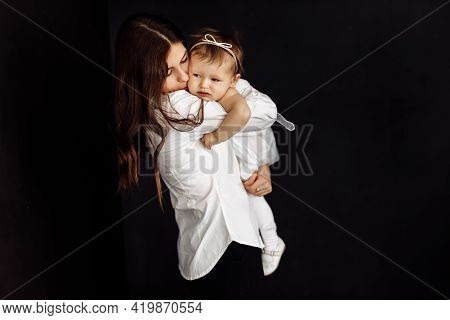 Dark-haired Young Mother Gently Holds In Her Arms And Hugs Little Daughter On Black Background, Happ