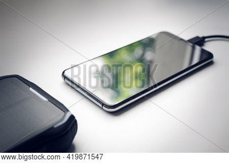 Solar Powerbank Charging Smartphone Next To A Window