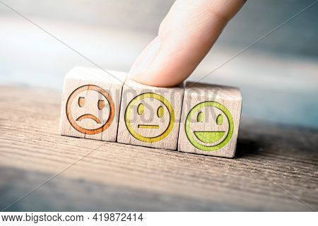 Average Feedback Concept With Red, Yellow And Green Smiling Faces On Wooden Blocks On A Board, The Y