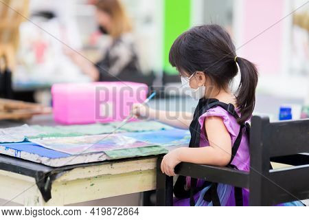 Selective Focus. Girl Wearing Cloth Face Mask Painting On Canvas. Kid Made Art Paint Watercolor. Chi