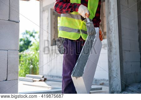 Close-up Hand Of Bricklayer Builder Working Autoclaved Aerated With Adhesive Plaster Concrete Blocks