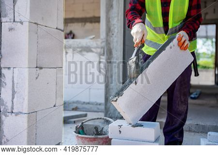 Close Up Of Bricklayer Builder Using Cement Mortar To Put The Lightweight Bricks. At Construction Si