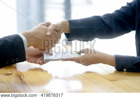 Businessman Shake Hand With Officer And Hold The Cash