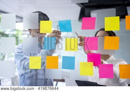 Business Women And Man Are Picking Up A Sticky Note