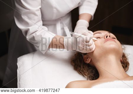 Skincare Spa And Cosmetology Salon Concept. Woman Receives Skincare Treatment In Beauty Clinic, Ther