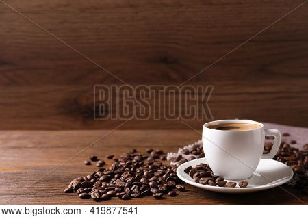 Cup Of Hot Aromatic Coffee And Roasted Beans On Wooden Table. Space For Text