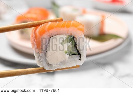 Chopsticks With Tasty Sushi Roll On Blurred Background, Closeup