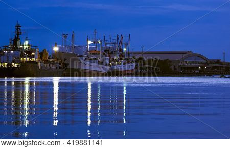 Large Oil Tanker And Fishing Boats Dock At Harbor In Industrial Area Along The River At Night