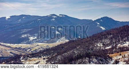 Mountainous Countryside Landscape In Early Spring. Leafless Forest On Snow Covered Hills And Meadows