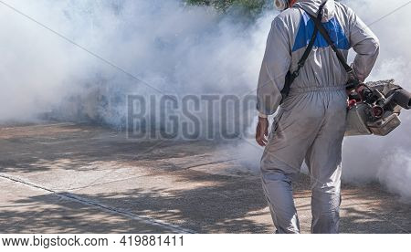 Midsection Of Outdoor Healthcare Worker In Protective Clothing Using Fogging Machine Spraying Chemic