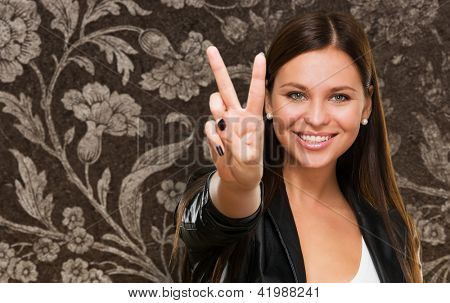 Beautiful Woman Giving Victory Sign against a vintage background