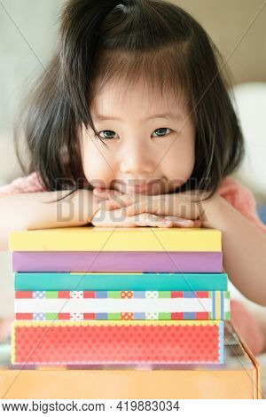 Vertical Image Of Asian Toddler Portrait Put Her Chin And Smiling Over Her Hands On Stack Of Books,