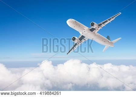 Passenger Airplane Flies In The Deep Blue Sky Over Cloudscape